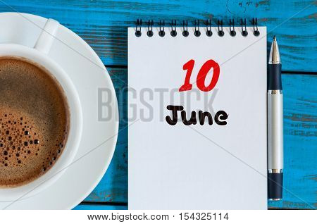 June 10th. Image of june 10 , calendar on blue background with morning coffee cup. Summer day, Top view.