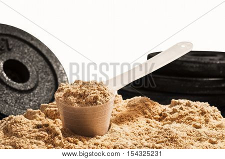 Product photograph of spoon or measuring scoop of whey protein on white background