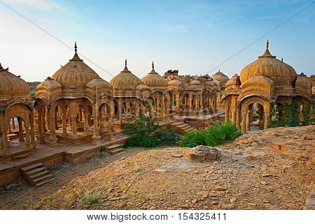 The royal cenotaphs of historic rulers also known as Jaisalmer Chhatris at Bada Bagh in Jaisalmer made of yellow sandstone at sunset