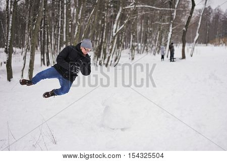 Freeze-frame - happy smiling young man jumped and falling on the snow in the Park in winter.