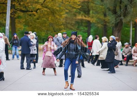Young cheerful long-haired girl in the hat the jacket and jeans dancing at a party in the Park among the people blur.
