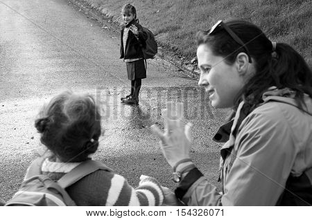 Little Girl Going To School Wave Goodbye To Her Mother And Sister