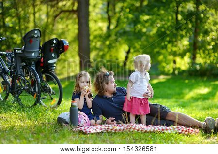 Young Father And His Daughters Having A Picnic