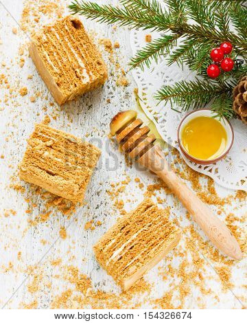 Winter Christmas honey cake on white wooden background with honey honey spoon christmas tree branch
