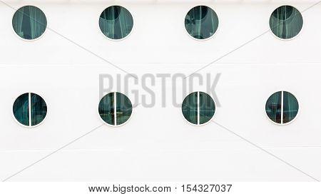 Eight Portholes on White Bulkhead of Cruise Ship