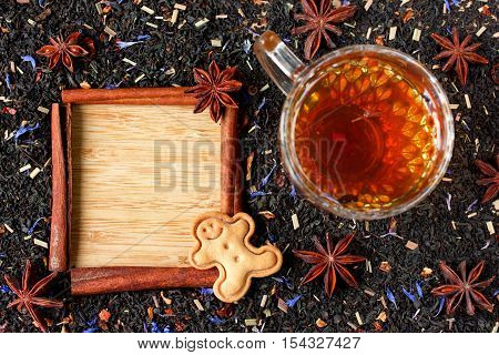 Winter tea background dried tea blend with herbs and spices and brewed tea in a cup cinnamon pod frame for text gingerbread man cookie top view