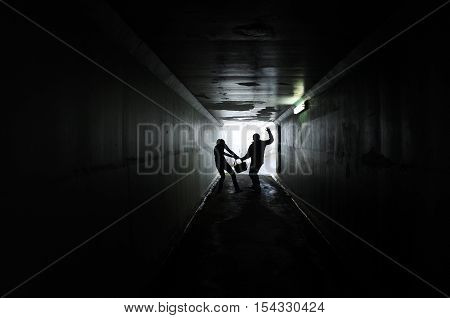 Silhouette of a man thief steals a bag from a woman in a dark tunnel. Violence against women concept. Real people copy space poster