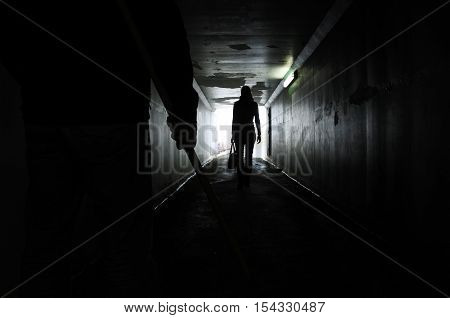 Man Follows A Young Woman In A Dark Tunnel