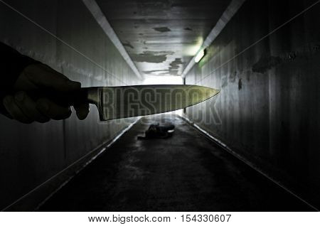 Man Hand Holds A Knife Over A Murder Victim In A Dark Tunnel