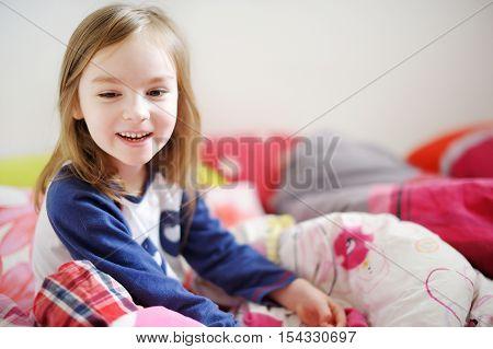 Little preschooler girl in pajamas on sunny morning