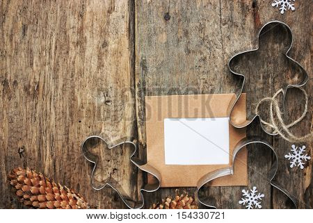 Vintage Christmas background with decorations and and blank greeting card on grunge wooden board