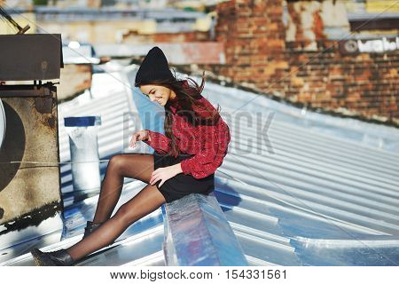 Cute long-haired girl sitting on an iron roof in windy and Sunny day against a brick wall and have fun laughing side view