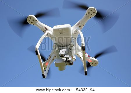 KAGAWA, JAPAN - OCTOBER 24, 2016: White remote controlled Drone Dji Phantom 3 equipped with high resolution video camera hovering in air and clear blue sky in the background