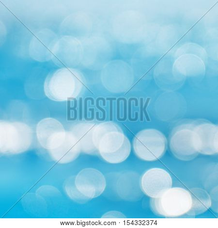 Sea blurred bokeh background with patches of light from sun.