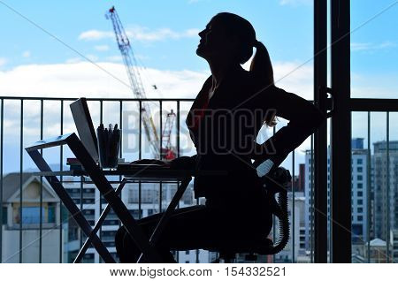Woman Having Back Pain While Working At Office Desk