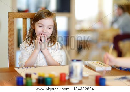 Cute Little Girl Is Drawing With Paints