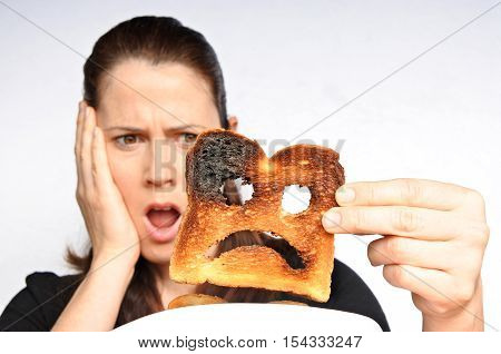 Shock Woman Holds A Burnt Slice Of Toast