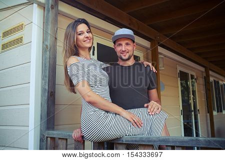 Caucasian who is sitting on the handrail and hugging her husband. Wearing striped dress. Posing at the camera and taking photos. They stand on the terrace of the wooden rest house