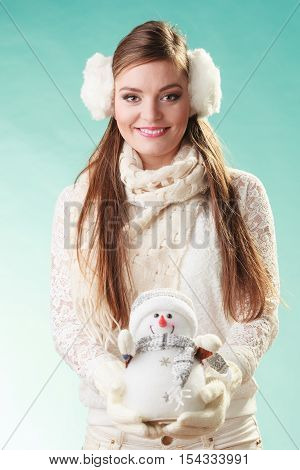 Smiling pretty cute woman holding little snowman. Attractive girl in earmuffs and white sweater pullover in studio on green. Winter fashion.