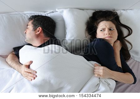 Man Hogging The Blanket From Woman In Bed