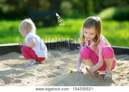 Two Little Sisters Playing In A Sandbox