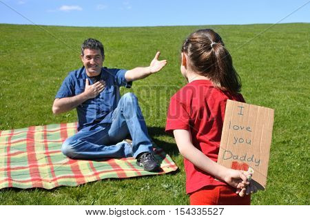 Young Girl Looks At Her Father And  Holds Behind Her Back A Card