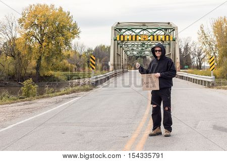 horizontal image of a homeless man standing on the highway in front of a steel bridge  holding up a sign for a ride on a grey fall day.