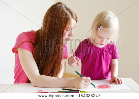 Young mother and her cute little toddler daughter drawing with colorful pencils at a daycare