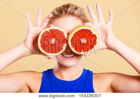 Woman fit girl holding two halfs of grapefruit citrus fruit in hands covering her eyes. Healthy diet food. Happiness holidays fun concept.