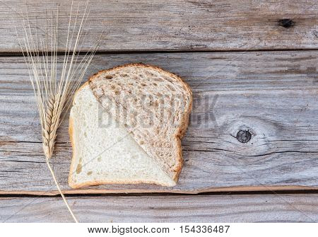 horizontal image of a white slice and a whole wheat slice of bread cut at an angle and put together as one slice placed on a rustic wood background with lots of room for text.