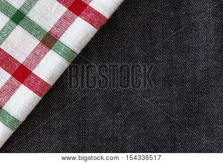 horizontal image of a denim background with a white and green and plaid material in the top corner.