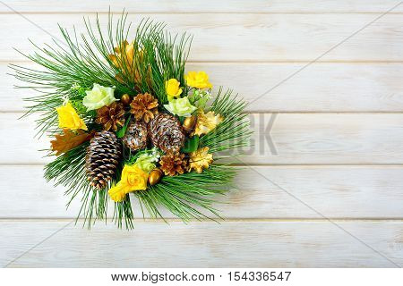 Christmas wreath with yellow silk roses and golden pinecones. Christmas party decoration. Christmas greeting background. Copy space.