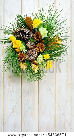 Christmas wreath with yellow fabric roses and golden pinecones. Christmas party decoration. Christmas greeting background. Copy space.