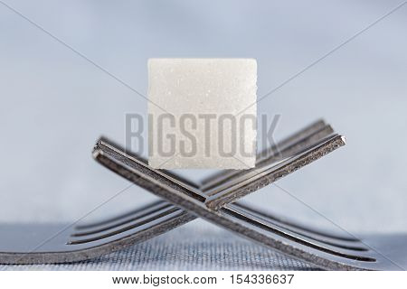 horizontal image of a sugar cube sitting on two forks intertwined as a platform for the sugar cube isolated on a light blue background