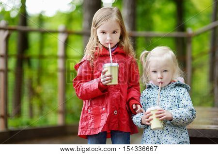 Two Little Sisters Drinking Hot Cholocate