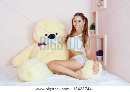Beautiful  Woman At Bed  With A Big Toy Bear.