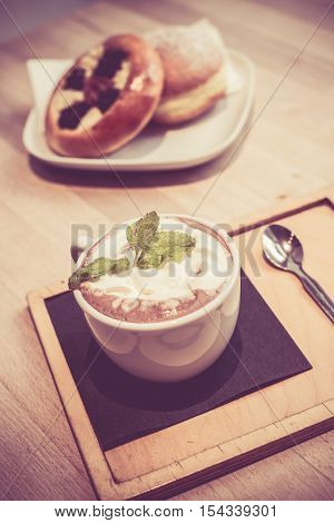Hot chocolate with bread mint on top vintage photo in coffee shop vintage photo