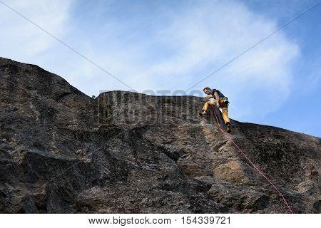 Rock climber, ascending the top. Success climbing on natural rocky wall.