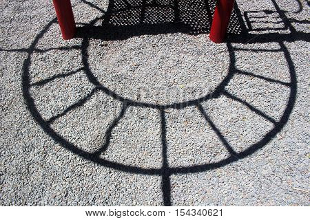 shadow of playground equipment on the gravel