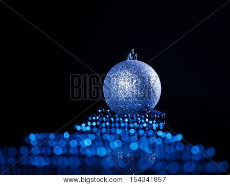 Silver christmas sphere with ribbon on black background. Christmas decoration. Celebration