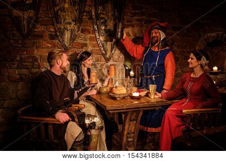 Medieval people eat and drink in ancient castle tavern