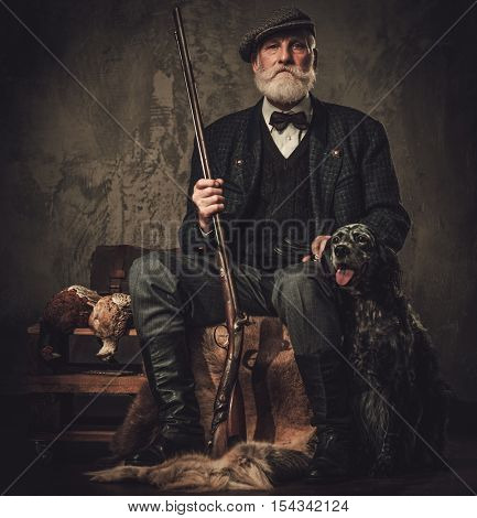 Senior hunter with a english setter and shotgun in a traditional shooting clothing, sitting on a dark background.