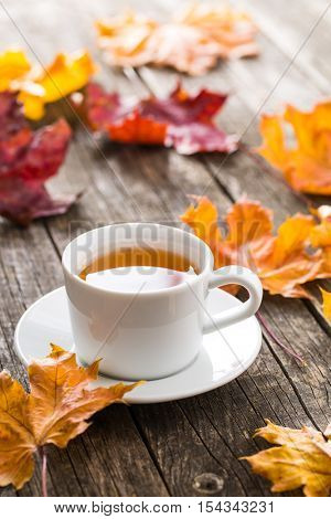 Cup of tea with autumn leaves on old wooden table.