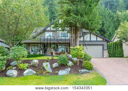Big custom made luxury house with nicely trimmed and landscaped front yard in the suburb of Vancouver, Canada.