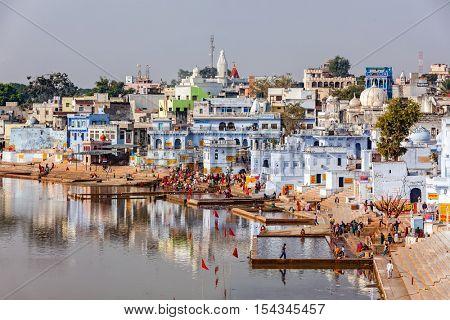 PUSHKAR, INDIA - NOVEMBER 20, 2012: Hindu devotees pilgrims bath in sacred Puskhar lake (Sagar) on ghats of Pushkar, Rajasthan. Pushkar is holy city for Hinduists and famous for many Hindu temples