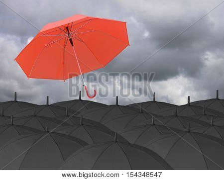 Red umbrella blown by wind and Surrounded by a black umbrellaconcept for management business idea on rain cloud background.