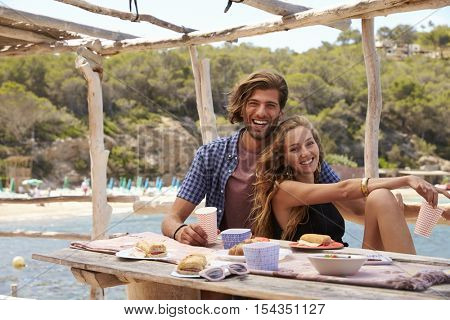 Young couple sitting at a table by the sea, look to camera