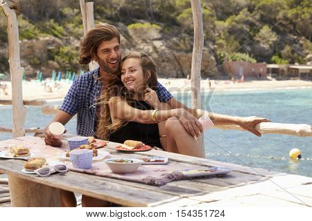Young couple sit at a table by the sea looking at each other