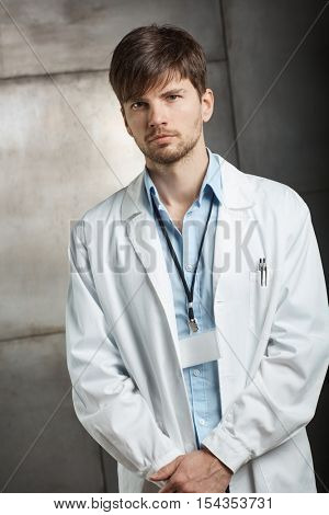 Portrait of serious young doctor standing in lab coat, looking at camera.