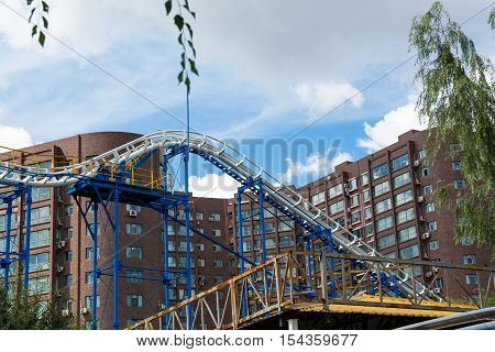 Sector of the roller-coaster with residential buildings on background. Not large blue and white roller-coaster.